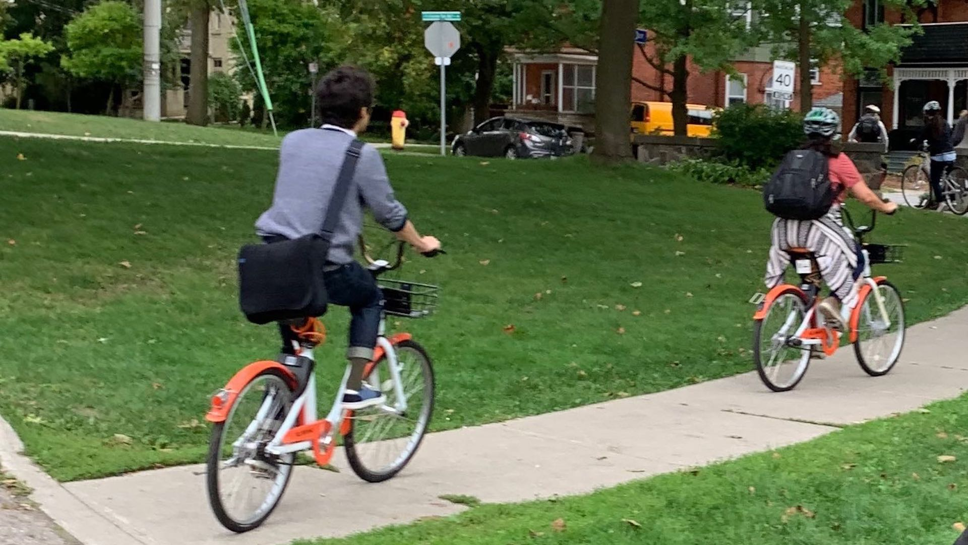 Two cyclists ride Dropbikes on a Kitchener street